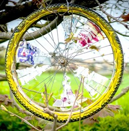 Decorated wheel in branches of tree