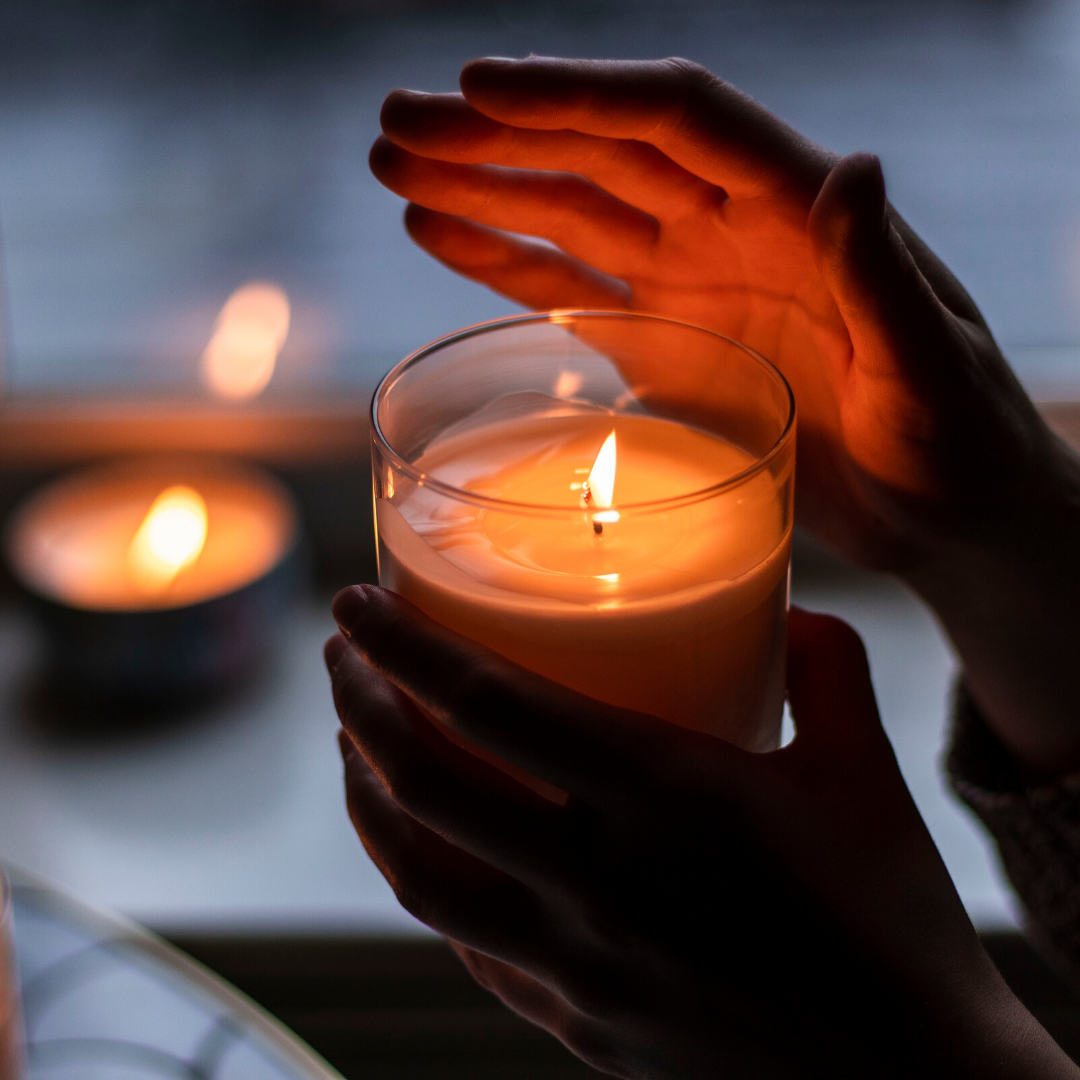 Person holding a lit candle