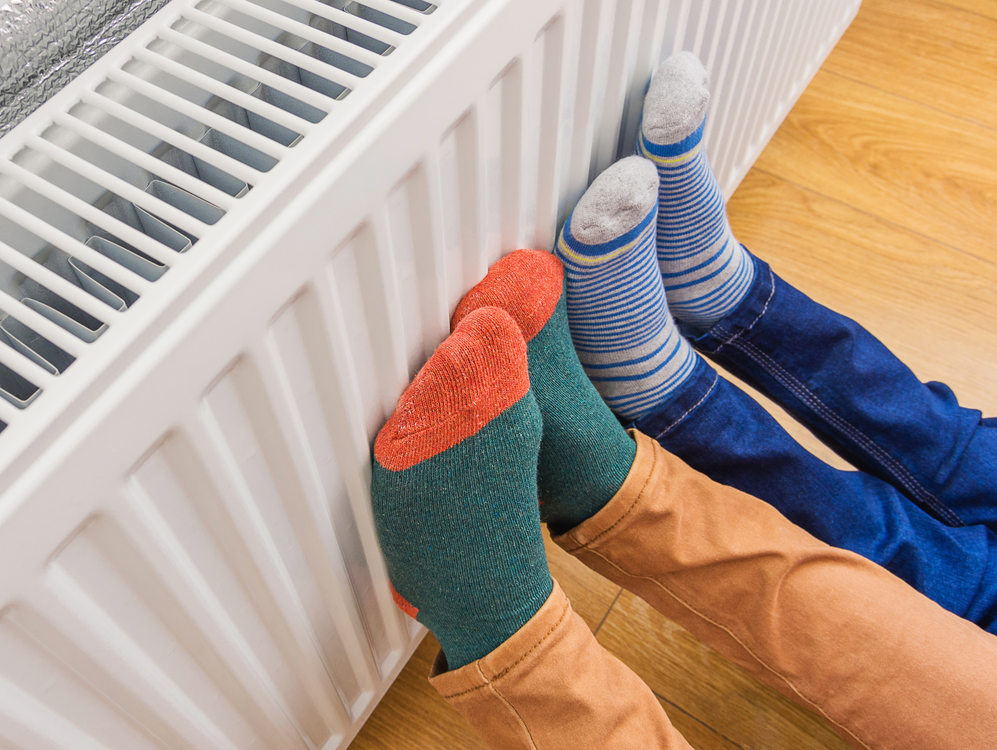 2 pairs of feet getting warm from a radiator
