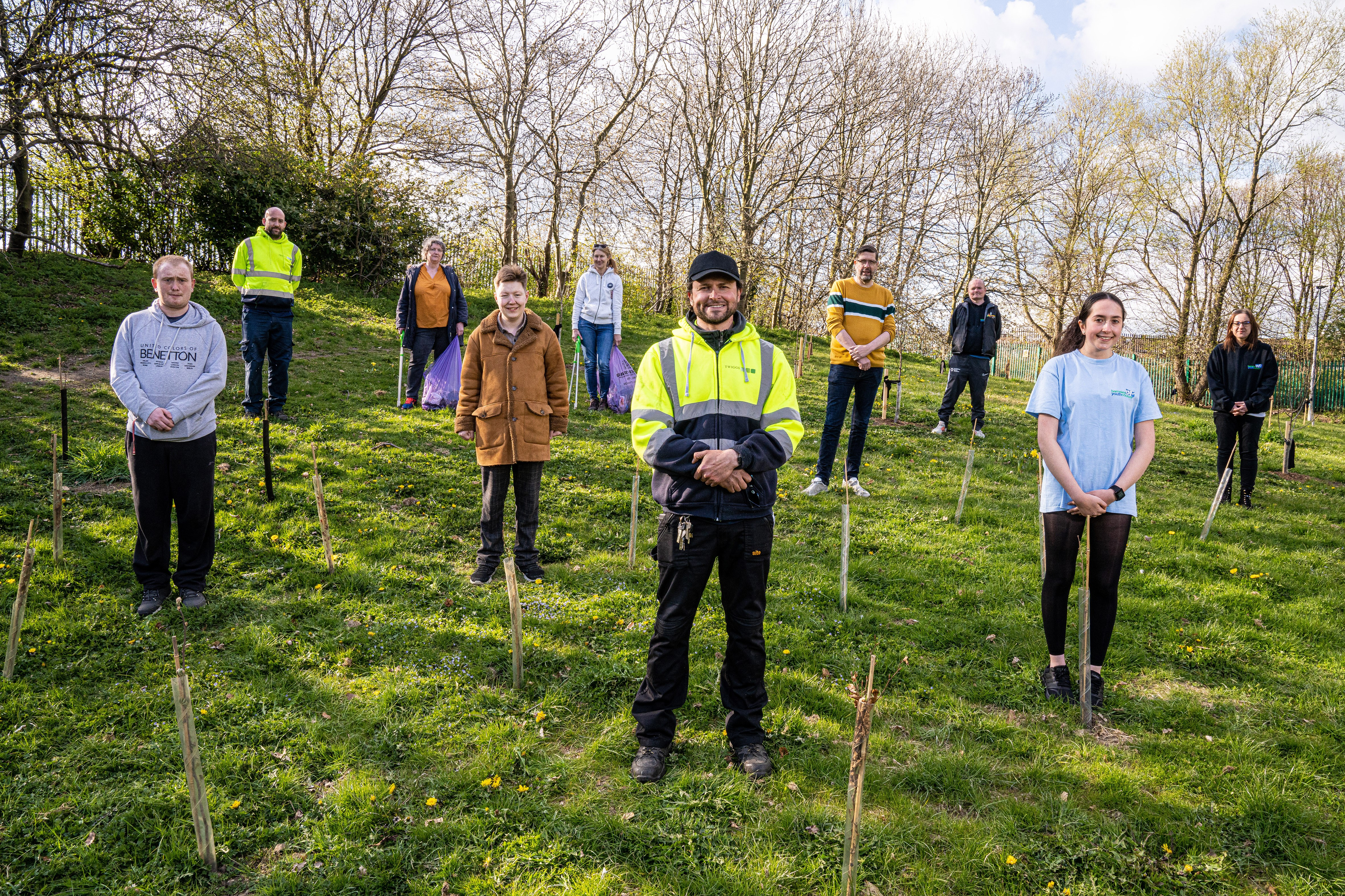 Group photo of young people and Twiggs planting trees