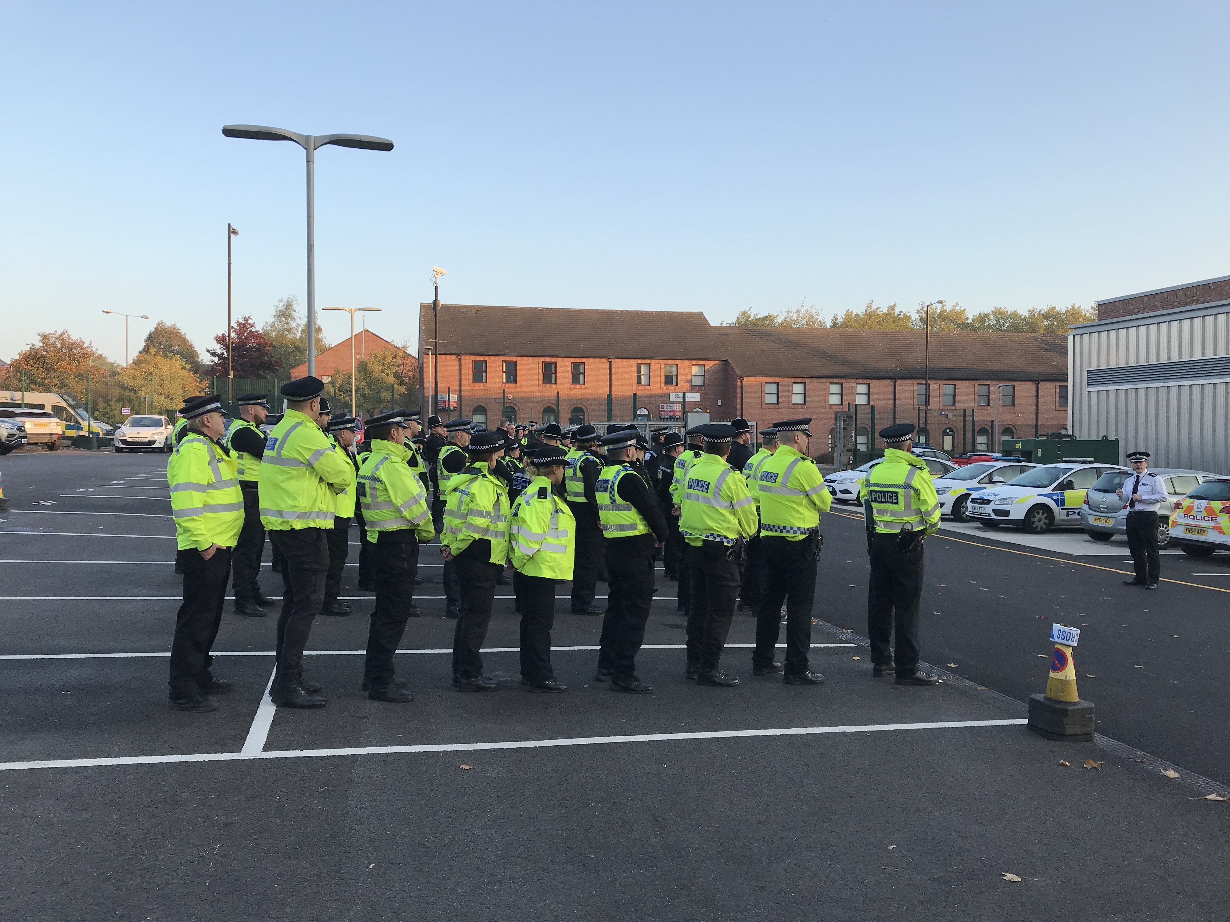 Police stood waiting in a car park